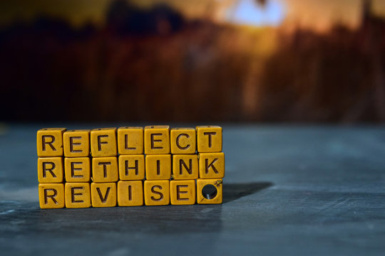 Reflect - Rethink - Revise on wooden blocks. Cross processed image with bokeh background