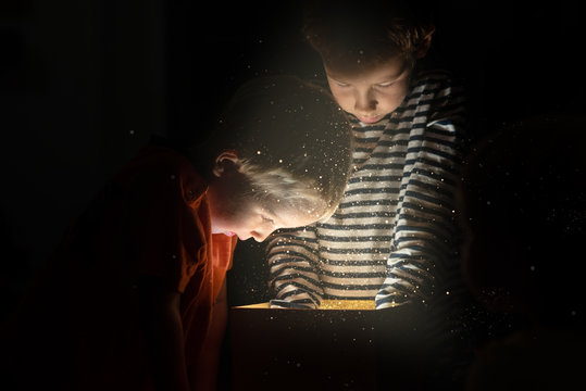 Two toddler boys standing over golden gift box with magical lights and glitters coming out