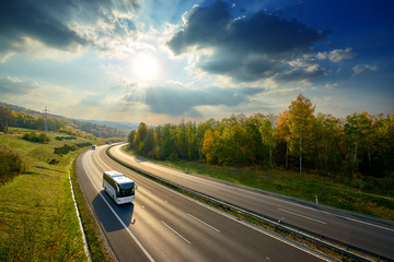 Fotobehang - Three white buses traveling on the asphalt highway between deciduous forest in autumn colors under the radiant sun and dramatic clouds. View from above.