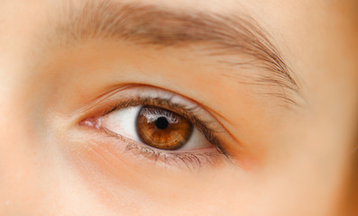Close-up shot of beautiful brown eye of little girl with reflection. No make up. Naturality concept