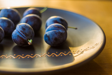 juicy blue plums in ceramic plate on wooden background