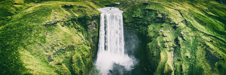 Stores photo Cascade Iceland waterfall Skogafoss banner nature landscape. Panoramic destination in Icelandic famous world landmark tourist attraction on South Iceland. Aerial drone view of top waterfall.