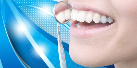 Woman teeth and a dentist mouth mirror on background
