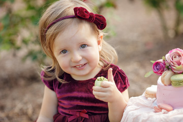 Little girl and decorated party with a cake in the flowers garden