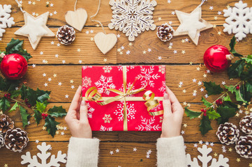 Woman hands holding Christmas present laid on a wooden table background