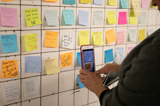 A woman stops to photograph messages written on Post-it notes displayed in the Union Sq subway station in New York City