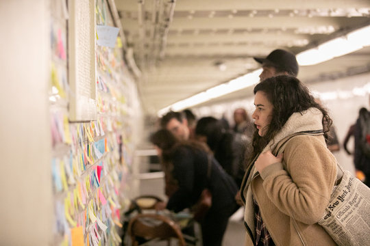 A woman stops to read messages written on Post-it notes displayed in the Union Sq subway station in New York City