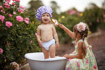 Little baby girl and her sister washing in bubble bath outdoor