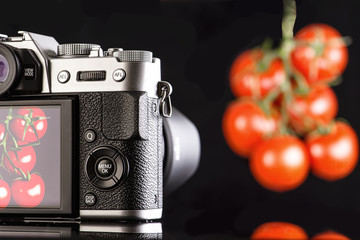 Photographing a tomato on a mirrorless camera on a black background.  Photographing food.