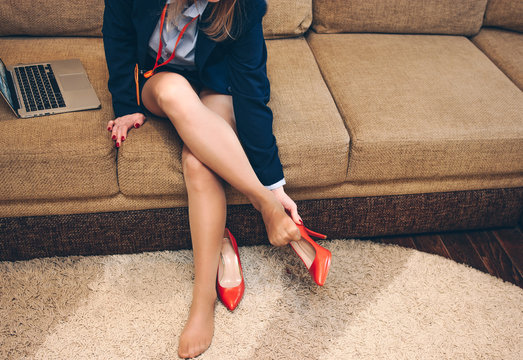 Business lady takes off high-heeled shoes after a working day at home.