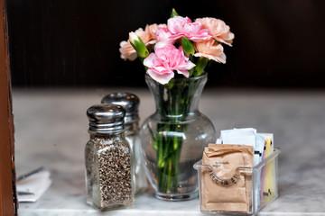 Closeup of salt, pepper and brown raw turbinado sugar shakers, packets, bottles on marble granite table, window in cafe restaurant, flowers in vase