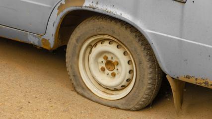Flat rear tire on old rusty car