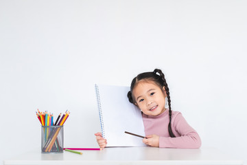 Asian girl kid doing drawing with many colour pencils on white paper over white background