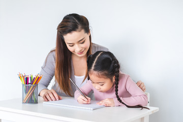 Asian girl kid and mother doing drawing with many colour pencils on white paper over white background