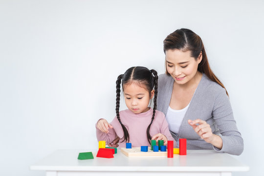 Asian girl daughter playing blocks toy with mother over white background, happy family concept