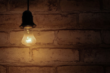 Brightly shining light bulb on a brick wall background. Energy saving concept. Background in a dark key, similar to the basement. Warm.