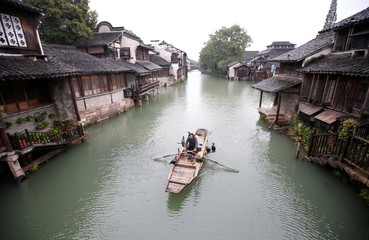 A fisherman pilots a boat with birds, known locally as fish hawks, perched onboard along a river in Wuzhen