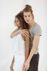 People in love, relationship, dating, lovers, romantic concept. Fashionable young mixed-race couple indoors standing in studio against white background. Portrait of interracial couple, Caucasian man