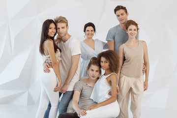 Friendship and relationship concept. Group of young multi-ethnic beautiful people wearing casual clothes posing together against white abstract polygonal background. Asian Caucasian Afro-American