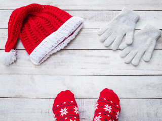 Selfie feet wearing red sock and handicraft Santa claus hat on vintage wood