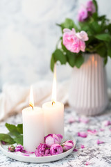 Cozy still life with candles and pink roses on a white table. Romantic home evening concept