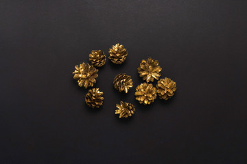 Pine cones colored in gold color on a black background. Minimalism. Concept of Happy New Year and Merry Christmas. Flat lay, top view