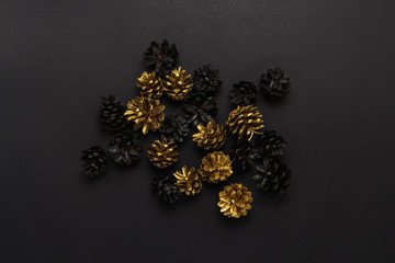 Pine cones painted in golden, black colors, Christmas-tree decorations on a black background. Minimalism. Concept of Happy New Year and Merry Christmas. Flat lay, top view