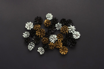 Pine cones painted in golden, black, white colors, Christmas-tree decorations on a black background. Minimalism. Concept of Happy New Year and Merry Christmas. Flat lay, top view