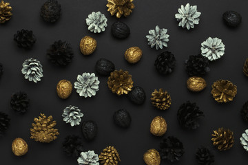 Pine cones and nuts painted in golden, black, white colors on a black background. Pattern. Concept of Happy New Year and Merry Christmas. Flat lay, top view
