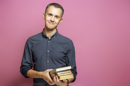 Young man holding a stack of books on a pink background.