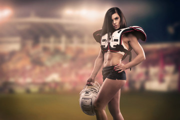 Athletic female dressed as an American Football Player. Real uniform, helmet, pads, ball.
