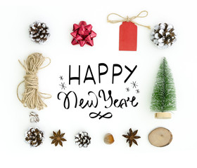 New Year greeting card . White ackground with hand lettering composition Happy New Year in frame of chtistmas tree toys, anise stars, fir cones, rope. Flat lay, top view of New Year 2019