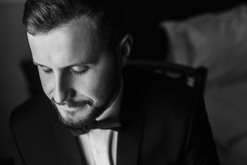 Stylish groom in black suit and bow tie, sitting in chair at window light. Confident and happy portrait of man. Groom getting ready in morning