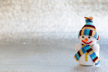 Christmas toy on a silver background with space for text. Christmas time. Snowman toy.
