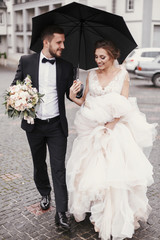 Gorgeous bride and stylish groom walking under umbrella in rainy street and smiling. Sensual wedding couple embracing. Romantic moments of newlyweds. Modern  wedding photo
