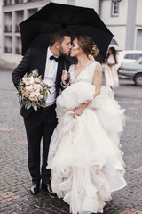 Gorgeous bride and stylish groom walking under umbrella in rainy street and kissing. Sensual wedding couple embracing. Romantic moments of newlyweds. Modern  wedding photo