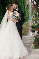 Gorgeous bride and stylish groom gently hugging on background of green trees. Sensual wedding couple embracing. Romantic moments of newlyweds. Modern wedding photo