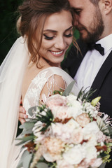 Gorgeous bride and stylish groom gently hugging and smiling on background of green trees. Sensual wedding couple embracing. Romantic moments of newlyweds. Wedding photo