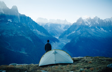 A hiker standing by his tent and looking at the mountains. Mont Blanc, Chamonix.