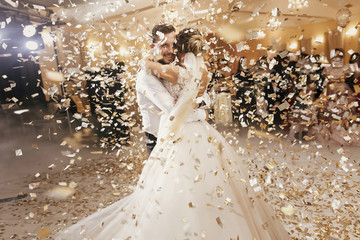Gorgeous bride and stylish groom dancing under golden confetti at wedding reception. Happy wedding...