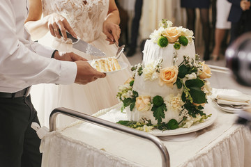 Gorgeous bride and stylish groom cutting together white wedding cake with roses at wedding reception. Happy wedding couple tasting cake. Romantic moments of newlyweds