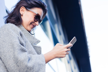 Below view of happy woman texting on smart phone.