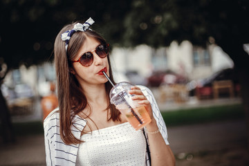 Happy hipster girl with sunglasses, in retro dress and headband, holding plastic cup and straw, drinking lemonade. Beautiful stylish young woman holding drink and relaxing in city street