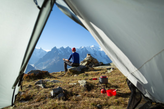 Hiker enjoying the view and a cup of coffe at his campsite in the mountains.