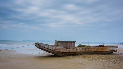 Papiers peints Pont Old fishing boat on the sea shore. Mong Kai, Vietnam