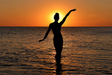 Silhouette of a mysterious female figure on the background of the sea sunset.