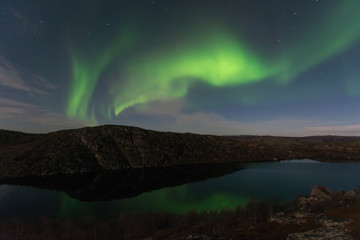 Northern lights, aurora in autumn over the lake.