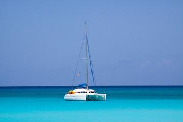 White catamaran anchored near the sunny coast of Half Moon Beach, Bahama´s.
