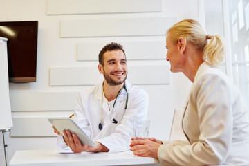 Arzt berät Patientin in Sprechstunde