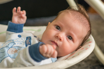 The newborn lies on swing automatic electrical chair and enjoys it